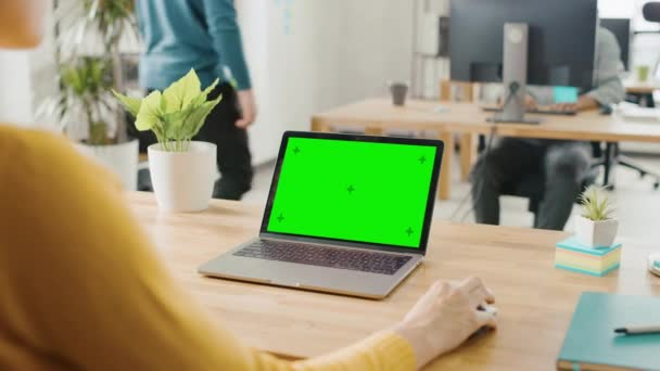 Over the Shoulder: Creative Young Woman Sitting at Her Desk Using Laptop with Mock-up Green Screen. Office where Diverse Team of Young Professionals Work on Computers