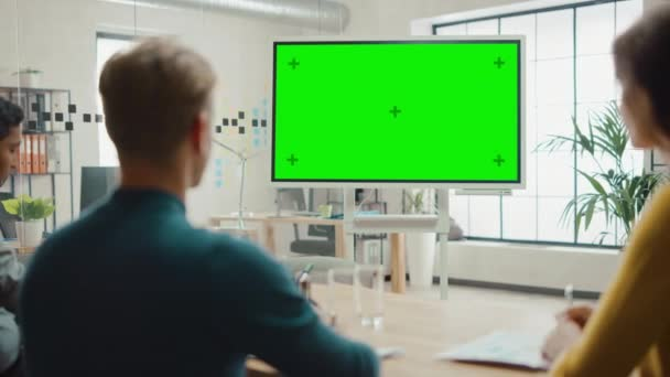 Team of Entrepreneurs Have a Meeting and Watch Green Screen Interactive Whiteboard. Young People Work in Creative Office