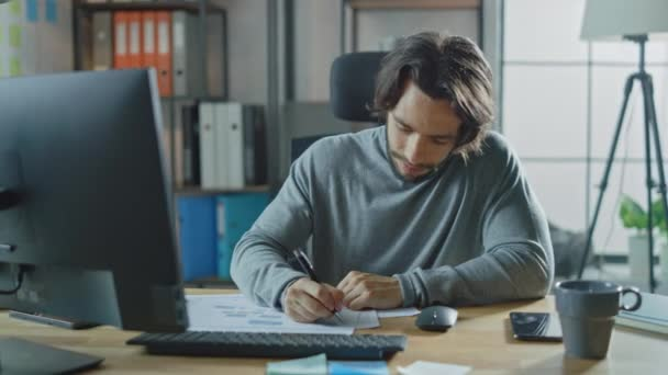 Handsome Long Haired Entrepreneur Sitting at His Desk in the Office Works on Desktop Computer, Working with Documents, Correcting Charts, Drawing Graphs, Statistic and Updating Company Strategy