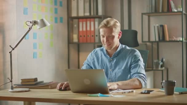 Handsome Blonde Businessman Sitting at His Desk in the Office Works on a Laptop. Creative Entrepreneur Using Computer Working on Software Unicorn Startup Project. Student Writing Paper for University
