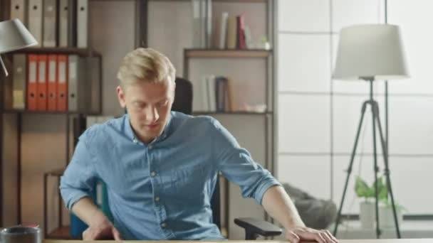 Handsome Young Entrepreneur Enters His Office sits at the Desk Opens Laptop and Starts Working on the Project. Businessman Using Notebook, Writing Email, Browsing Internet, Designing Startup Software