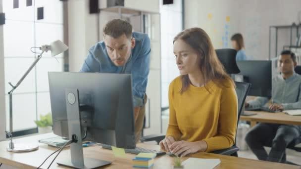 Spezialistin arbeitet am Desktop-Computer, Projektmanagerin steht daneben und gibt Ratschläge zur Optimierung des Workflows für Customer Experience Management. Modernes Büro mit vielseitigem Team von Fachleuten