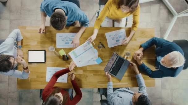 Startup-Besprechungsraum: Team von Unternehmern, die am Konferenztisch sitzen, diskutieren, lösen Probleme, verwenden digitales Tablet, Laptop, teilen Dokumente mit Statistiken, Diagramme. von oben heranzoomen