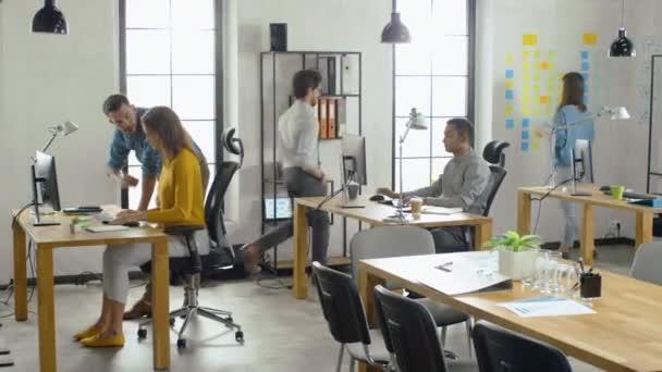 Specialistka pracuje na stolním počítači, projektový manažer stojí vedle a poskytuje rady ohledně optimalizace pracovního postupu pro řízení zkušeností zákazníků. Moderní kancelář s rozmanitým týmem profesionálů