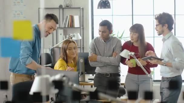 Die Fachfrau arbeitet am Desktop-Computer, die Projektmanagerin sitzt am Tisch daneben und gibt Ratschläge zur Optimierung des Workflows für das Customer Experience Management. Büro mit vielseitigem Team von Fachleuten