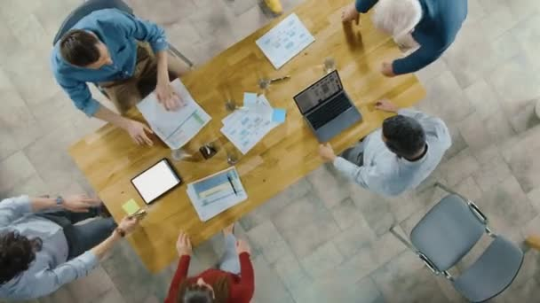 Startup Meeting Room: Team of Entrepreneurs sitting at the Conference Table Have Discussions, Solve Problems, Use Digital Tablet, Laptop, Share Documents with Statistics, Charts. Top View Zoom In