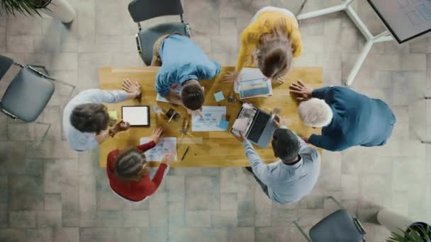 Startup Meeting Room: Team of Entrepreneurs Standing Around Conference Table Have Discussions, Solve Problems, Use Digital Tablet, Laptop, Share Documents with Statistics, Charts. Top View Camera Shot