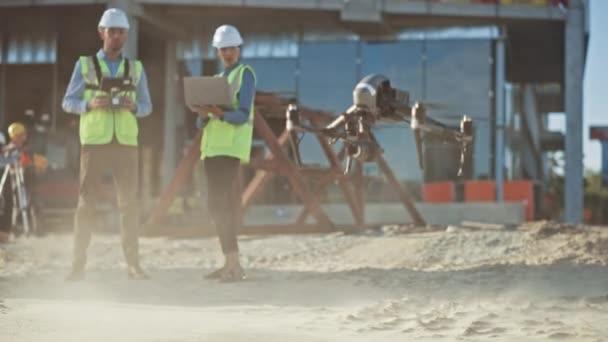 Rozmanitý tým specialistů pilot je na staveništi. Inženýr architektury a inspektor bezpečnostní techniky Fly Drone na stavbě komerčních budov kontrola designu a kvality