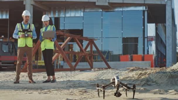 Dva specialisté ovládají Drone na staveništi. Inženýr architektury a bezpečnostní inspektor Fly Drone na stavbě komerčních budov technická kontrola desing a kvality