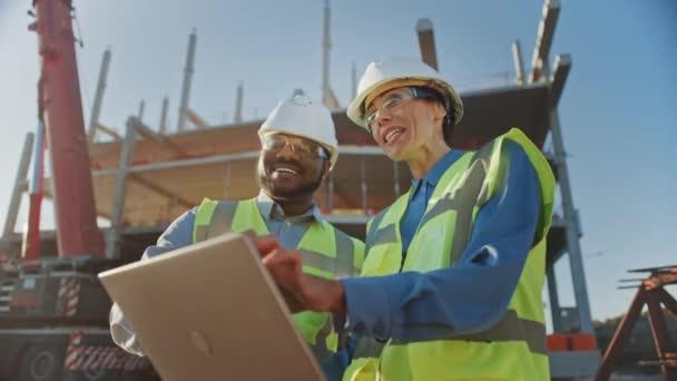 Dva specialisté: Prozkoumejte obchodní, průmyslové stavební staveniště. Projekt realit s civilním inženýrem, investor používá přenosný počítač. V pozadí jeřábu, rámy pro betonovou formování mrakodrapu