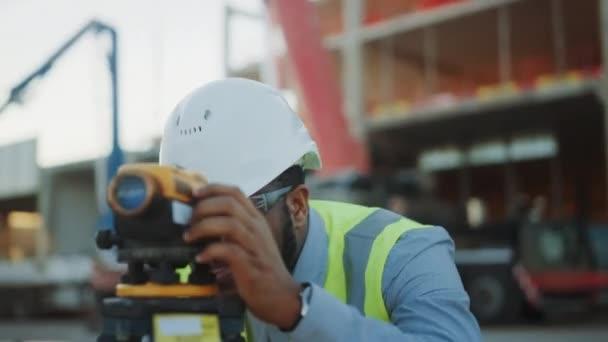 A kereskedelmi/ipari épület építőipari site: szakmai mérnök Surveyor úgy intézkedések teodolit, munkás használ laptop. A háttérben felhőkarcoló zsalut keretek és daru