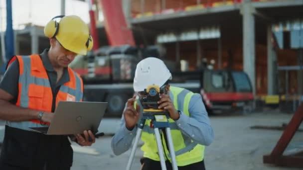 V rámci staveniště komerčního/průmyslového stavebnictví: profesionální inženýr, který provádí opatření s Teodolitem, používá digitální tabletový počítač. Ve formací rámy a jeřábu na pozadí mrakodrapu