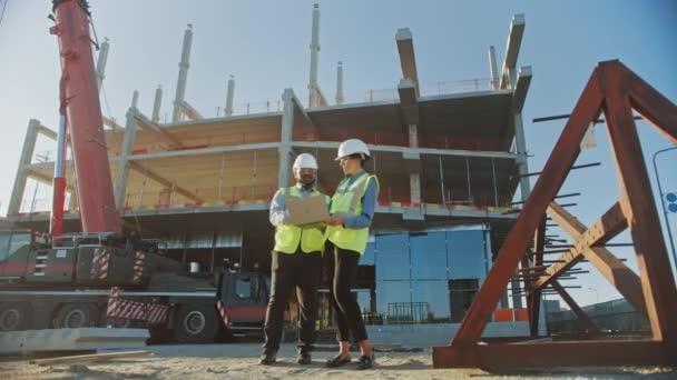 Két specialisták vizsgáljuk kereskedelmi, ipari építőipari site. Real Estate projekt építőmérnök, befektetői use laptop. A háttérben Crane, Skyscraper beton zsaluk keretek