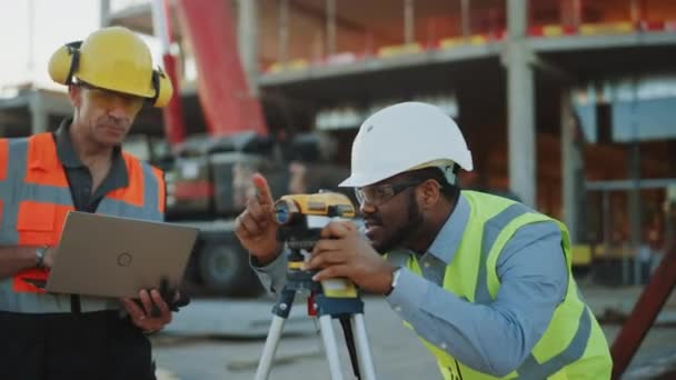 On the Commercial / Industrial Building Construction Site: Professional Engineer Surveyor Takes Measures with Theodolite, Worker Uses Laptop. In the Background Skyscraper Formwork Frames and Crane