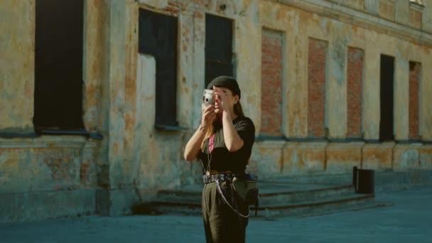Cooles, künstlerisch wirkendes junges Mädchen mit Mütze und runder Brille fotografiert mit Filmkamera im Hipster-Stadtviertel. stylische brünette Teenager fotografiert kulturell hippe Gebäude