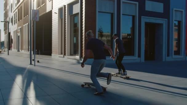 Dva profesionální bruslaře jezdíš na skateboardy skrz módní čtvrť Hipster. Pohledný chlápek skateboarding přes moderní městskou ulici. Následující snímek s pomalým pohybem fotoaparátu