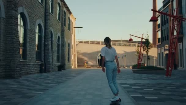 Group of Girls and Guys Riding on Skateboards Through Fashionable Hipster District. Beautiful Young People Skateboarding Through Modern City Street. Following Slow Motion Camera Shot