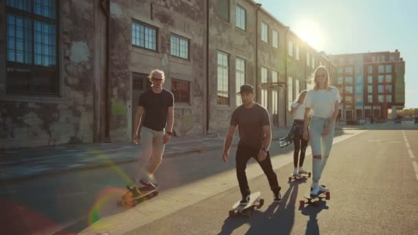 Group of Girls and Boys on Skateboards Ride Through Fashionable Hipster District. Beautiful Young People Skateboarding Through Modern Stylish City Street. Moving Slow Motion Portrait Camera Shot