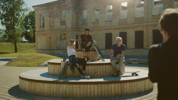 Stylish Cool Teenagers Chilling on the Benches in the Park. Two Girls and Two Boys Resting with Their Skateboards, Talking and Having Fun. Stylish Post Industrial Park In Gentrified Part of City