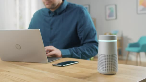 Photo Man Sitting at His Desk Works on Laptop, Beside Him Smart Speaker with Artificial Intelligence Assistance Answers Questions, Plays Music, Podcast. Speaker Shows Equalizer Lights