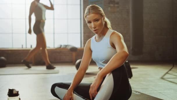 Portrét nádherné, silně zapadly světlé posezení v podkrovní tělocvičně s motivačními plakáty. Chytne svůj dech po tréninku intenzivní fitness. Tvář sportovce zobrazená zblízka.