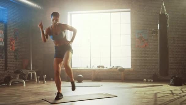 Silná a fit krásná atletická žena ve sportu Top a šortky má stálý březen cvičení ve stylu podkroví průmyslová tělocvična s motivačními plakáty. To je tréninkový trénink.