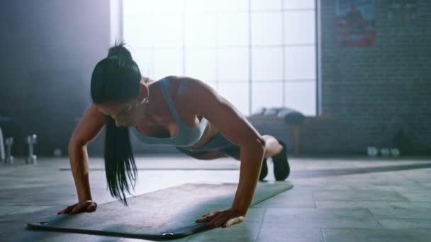 Silná a fit atletická žena ve sportu Top a šortky dělá cvičné cvičení ve stylu podkroví průmyslová tělocvična s motivačními plakáty. Je to součást cvičení pro kondiční výcvik.