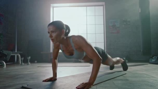 Silná a fit atletická žena ve sportu Top a šortky se účastní cvičení ve stylu podkroví průmyslová tělocvična s motivačními plakáty. Je to součást cvičení pro kondiční výcvik.