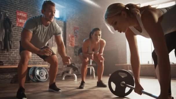 Mužské a ženské fitness trenéři Podporovat krásné fit atletické mladé ženy ve svém denním cvičení. Úspěšně zvedá těžkého Barbella. Školení se koná v tělocvičně s motivačními plakáty.