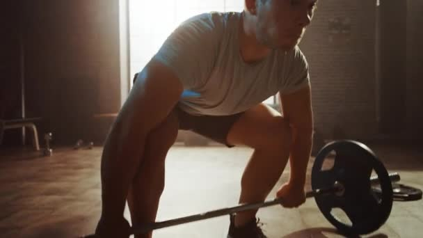 Handsome Muscular Man Does Overhead Deadlift with a Barbell in a Small Authentic Gym. Athletic Man Training His Arm Muscles and Exercises with Barbell. Workout in the Hardcore Gym. Arc Shot.