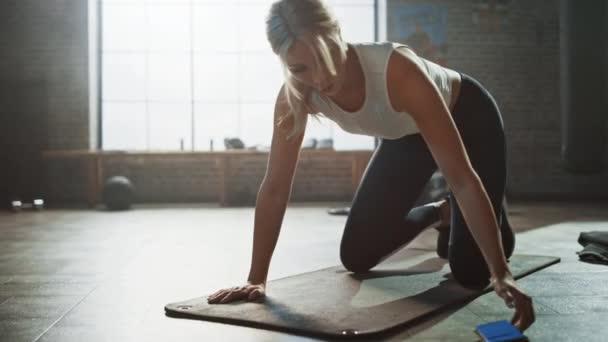 Krásná a mladá dívka používá smartphone aplikaci k instalačnímu programu pro její cvičení a začíná běžet na její fitness rohoži. Sportovní žena dělá horolezectví ve stylovém hardcore tělocvičně
