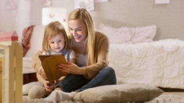Beautiful Mother and Her Little Daughter Have Good Time Reading Children's Books on a Tablet Computer. Sunny Living Room.