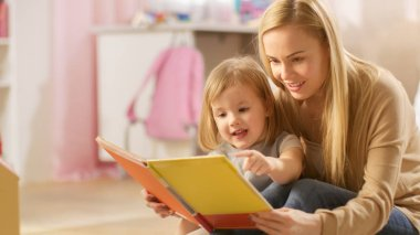 Beautiful Young Mother and Her Cute Little Daughter Read Children's Book Together. Children's Room is Pink and Full of Toys.