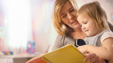 Close-up Shot of a Beautiful Young Mother and Her Cute Little Daughter Read Children's Book Together. Children's Room is Pink and Full of Toys.