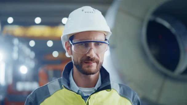 Porträt eines lächelnden professionellen Schwerindustrie-Ingenieurs / Arbeiters in Schutzuniform, Brille und Hut. Im Hintergrund unkonzentrierte große Industriefabrik