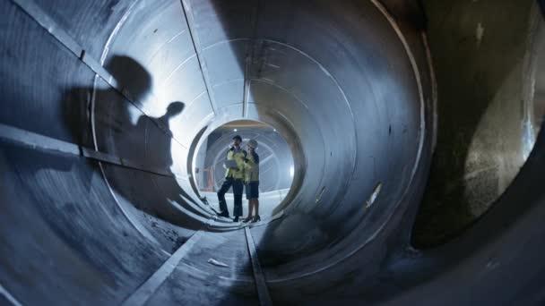Zwei Schwerindustrie-Ingenieure gehen in Rohr, verwenden Laptop, diskussionen, überprüfen Design. Bau der Transportpipeline für Öl, Erdgas und Brennstoffe. Industrielle Fertigungsfabrik
