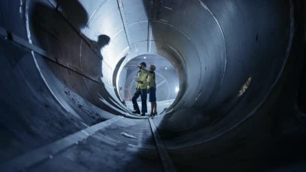 Két nehézipari mérnökök gyaloglás Inside pipe, használata laptop, have vita, ellenőrzése design. Az olaj-, földgáz-és bioüzemanyag-szállítási csővezeték építése. Ipari Gyártógyár