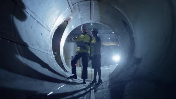 Zwei Schwerindustrie-Ingenieure, die im Rohr wandeln, Laptop benutzen, diskutieren, Design prüfen. Bau der Transportpipeline für Öl, Erdgas und Biokraftstoffe. Fabrik für industrielle Fertigung
