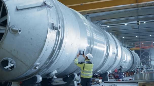 Schwerindustrie-Ingenieur verwendet digitales Augmented-Reality-Tablet zum Scannen von Rohren mit großem Durchmesser Moderne industrielle Fertigungstechnologie zur Planung und Konstruktion von Öl-, Gas- und Kraftstofftransport-Pipelines.