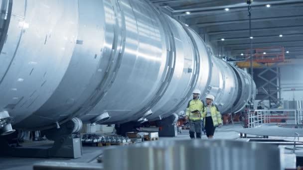 Zwei Ingenieure der Schwerindustrie, die durch die Rohrfertigungsanlage laufen, digitales Tablet verwenden, Diskussionsstoff führen. Modernes Industriedesign und Bau von Öl-, Gas- und Kraftstofftransportpipeline