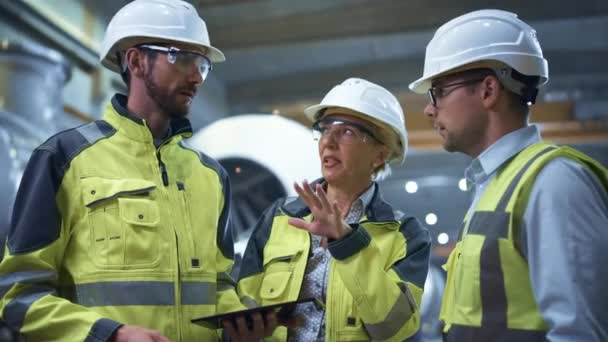 Tři těžké průmyslové inženýři stojí v továrně na výrobu trubek, Použijte digitální tablet počítače, Diskuse. Velká trubka smontována. Návrh a konstrukce ropovodu, plynu a pohonných hmot