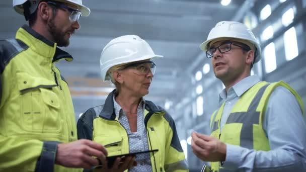 Tři těžké průmyslové inženýry v továrně na výrobu trubek, použití digitálního tabletového počítače, diskuse. Velká trubka smontována. Návrh a výstavba plynovodu pro ropu, zemní plyn a paliva