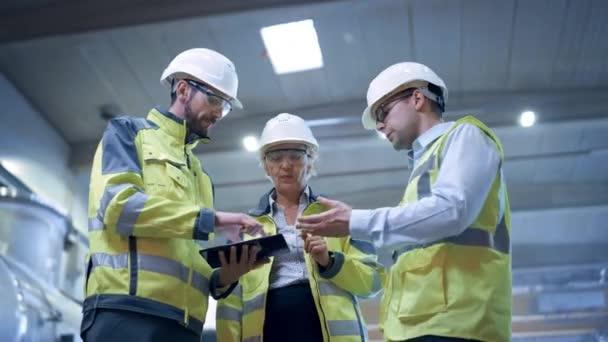 Drei Schwerindustrie-Ingenieure stehen in der Rohr-Fertigungsfabrik, nutzen digitale Tablet-Computer, diskutieren. Planung und Bau einer großen Öl-, Gas- und Kraftstofftransport-Pipeline. Niedriger Winkel