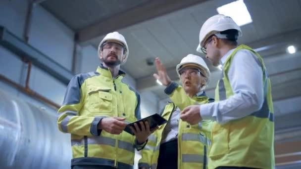 Drei Schwerindustrie-Ingenieure stehen in der Rohrfertigungsfabrik, benutzen digitale Tablet-Computer, diskutieren. Planung und Bau einer großen Öl-, Gas- und Treibstoff-Transportleitung. niedriger Winkelbogen