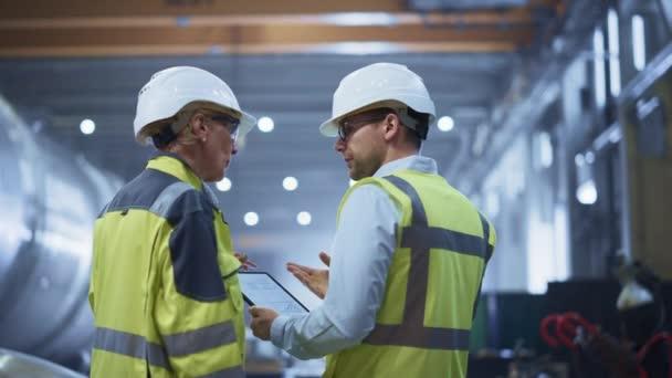 Dva z těžkých průmyslových inženýrů v továrně na výrobu trubek, použití digitálního tabletového počítače, diskuse. Výstavba potrubní přepravy ropy, zemního plynu a paliv. Zpět zobrazit odletující jiskry