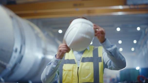Porträt eines jungen professionellen Schwerindustrie-Ingenieurs / Arbeiters, der Sicherheitsweste trägt und einen Hut aufsetzt. Im Hintergrund eine unkonzentrierte große Industriefabrik, in der Schweißfunken fliegen. Zeitlupe
