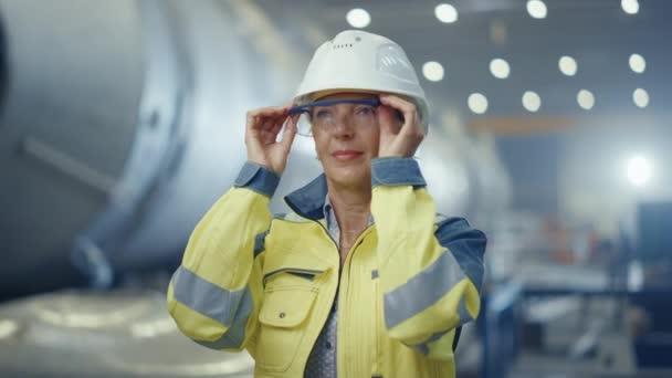 Porträt einer Ingenieurin aus der Schwerindustrie, die Schutzuniform und Hut trägt und die Schutzbrille abnimmt. Im Hintergrund unfokussierte große Industriefabrik, in der Schweißfunken fliegen