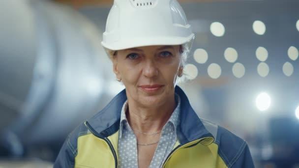 Porträt einer Ingenieurin aus der Schwerindustrie, die Sicherheitsuniform und Hut trägt und charmant lächelt. Im Hintergrund eine unkonzentrierte große Industriefabrik, in der Schweißfunken fliegen