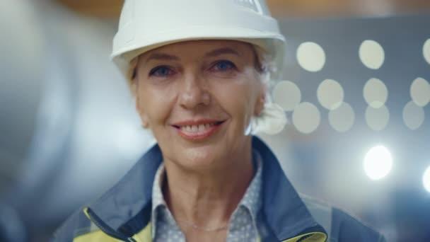 Porträt der professionellen Schwerindustrie weibliche Ingenieur trägt Sicherheitsuniform und harten Hut, lächelnd Charmant. Im Hintergrund unfokussierte große Industriefabrik, wo Schweißen Funken fliegen