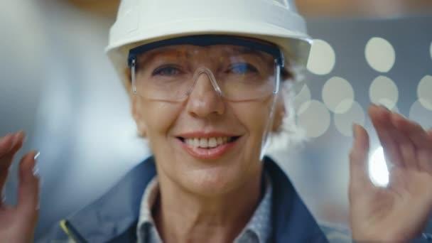 Porträt einer professionellen Ingenieurin aus der Schwerindustrie, die Schutzuniform und Hut trägt, die Brille abnimmt und charmant lächelt. Im Hintergrund unfokussierte große Industriefabrik, in der Schweißfunken fliegen